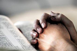Zum Beten gefaltete, auf der Bibel liegende Hände