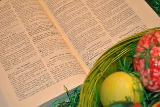 Bunte Ostereier neben aufgeschlagener Bibel